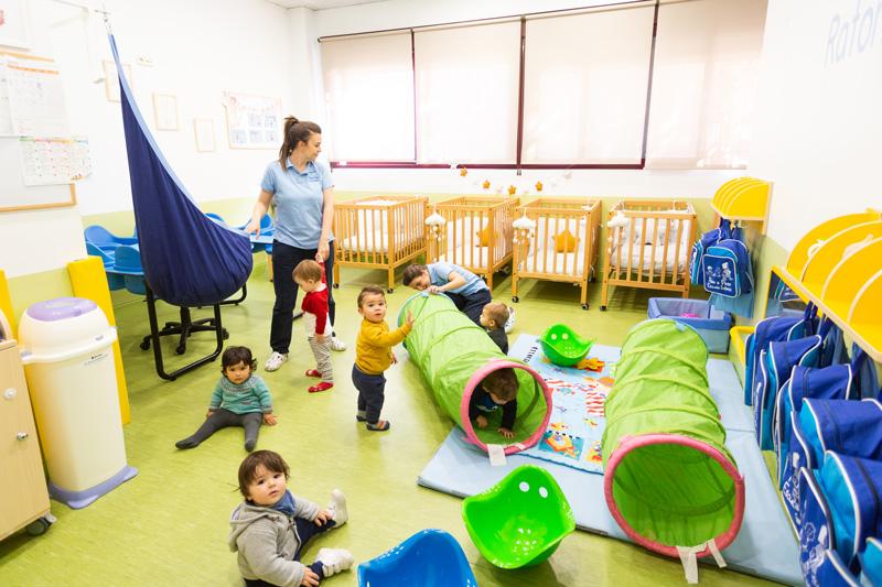 niños jugando en el aula con la profesora
